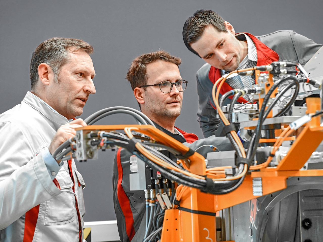 Peter Stechel (Head of the Analysis Center, left), Ralf Hofmeister (Head of the technical center for body measurement technology), and Thomas Reeb (Head of measurement technology, right) examine sensors on an inline measuring station at the Ingolstadt plant.