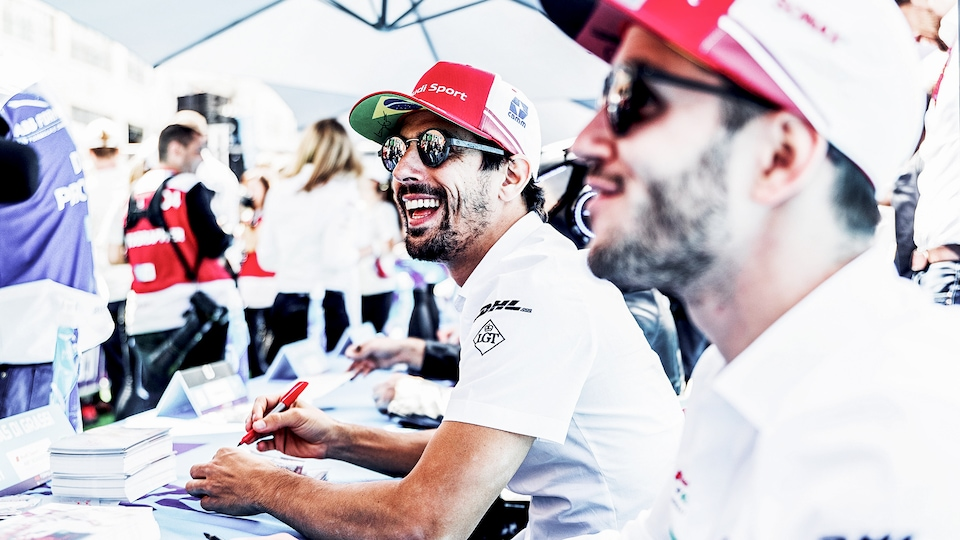 Lucas di Grassi and Daniel Abt writing autographs