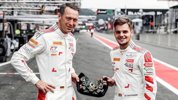 Frank Stippler and Dries Vanthoor holding a steering wheel