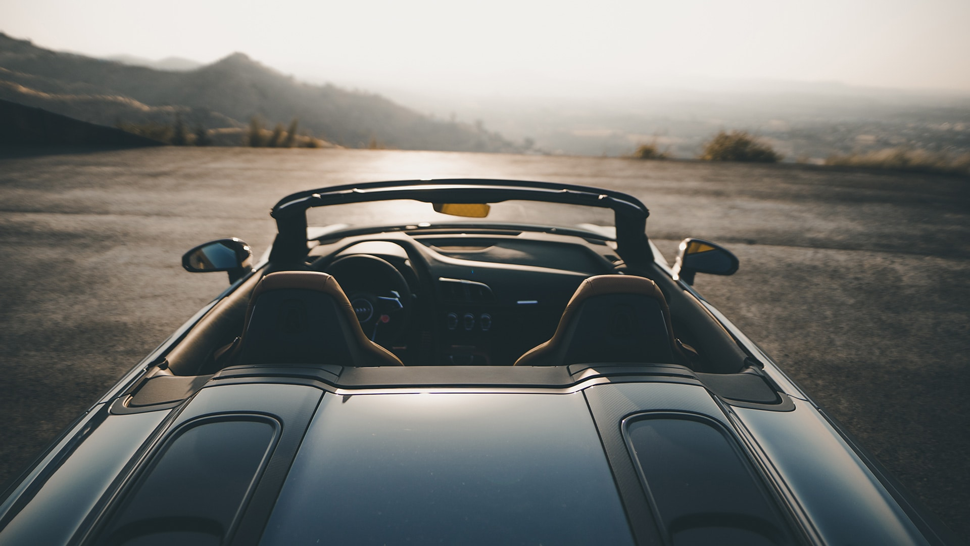 The R8 Spyder has a lightweight soft top which tapers into two fins. These stretch the cloth so that it harmonizes perfectly with the athletic design of this high-performance sports car, in much the same was as the large CFRP hood compartment cover does.