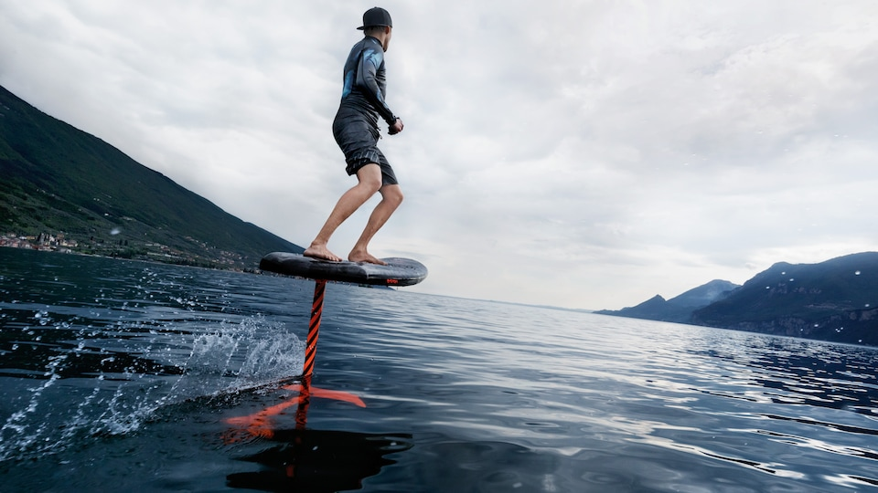 Franz Hofmann tests the prototype Audi e-foil on Lake Garda. The battery is integrated into the board, the jet-propulsion system sits on the foil in the water, with Hofmann using a remote control in his right hand to regulate the speed.