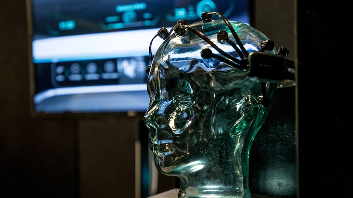 A glass model of a human head wearing the Brain Computer Interface