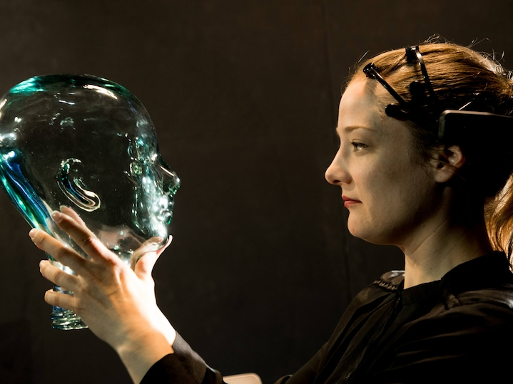 Woman holding a glass model of a human head