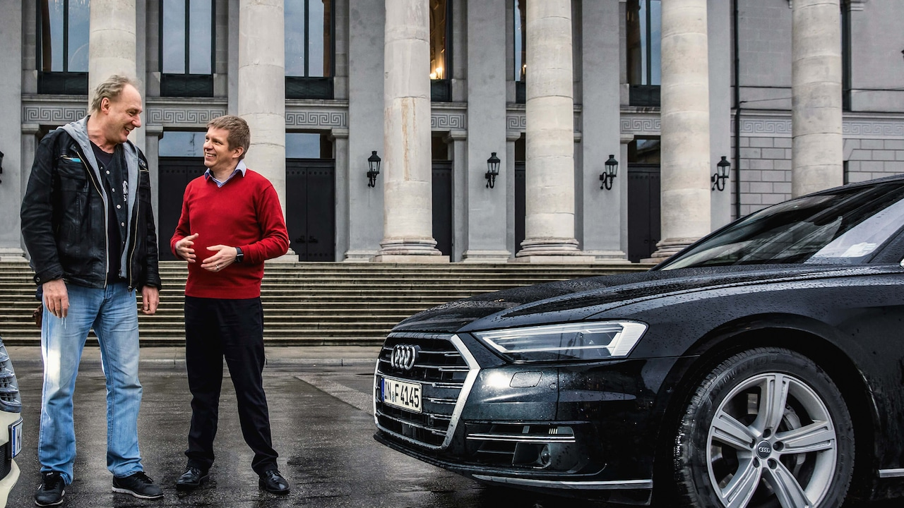 Two men standing next to an Audi A8