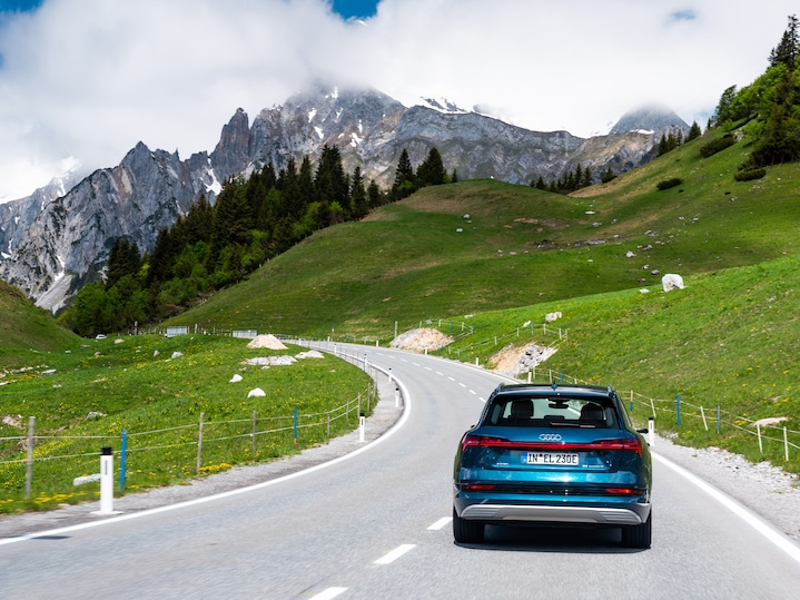A rear view of the Audi e-tron electric car in the mountains.
