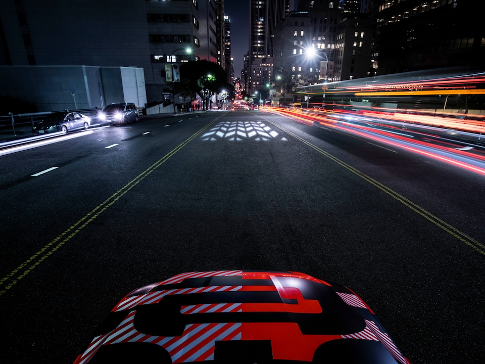 A global innovation made by Audi: The fully electric Audi e-tron Sportback follows the carpet of light it is projecting onto the streets.