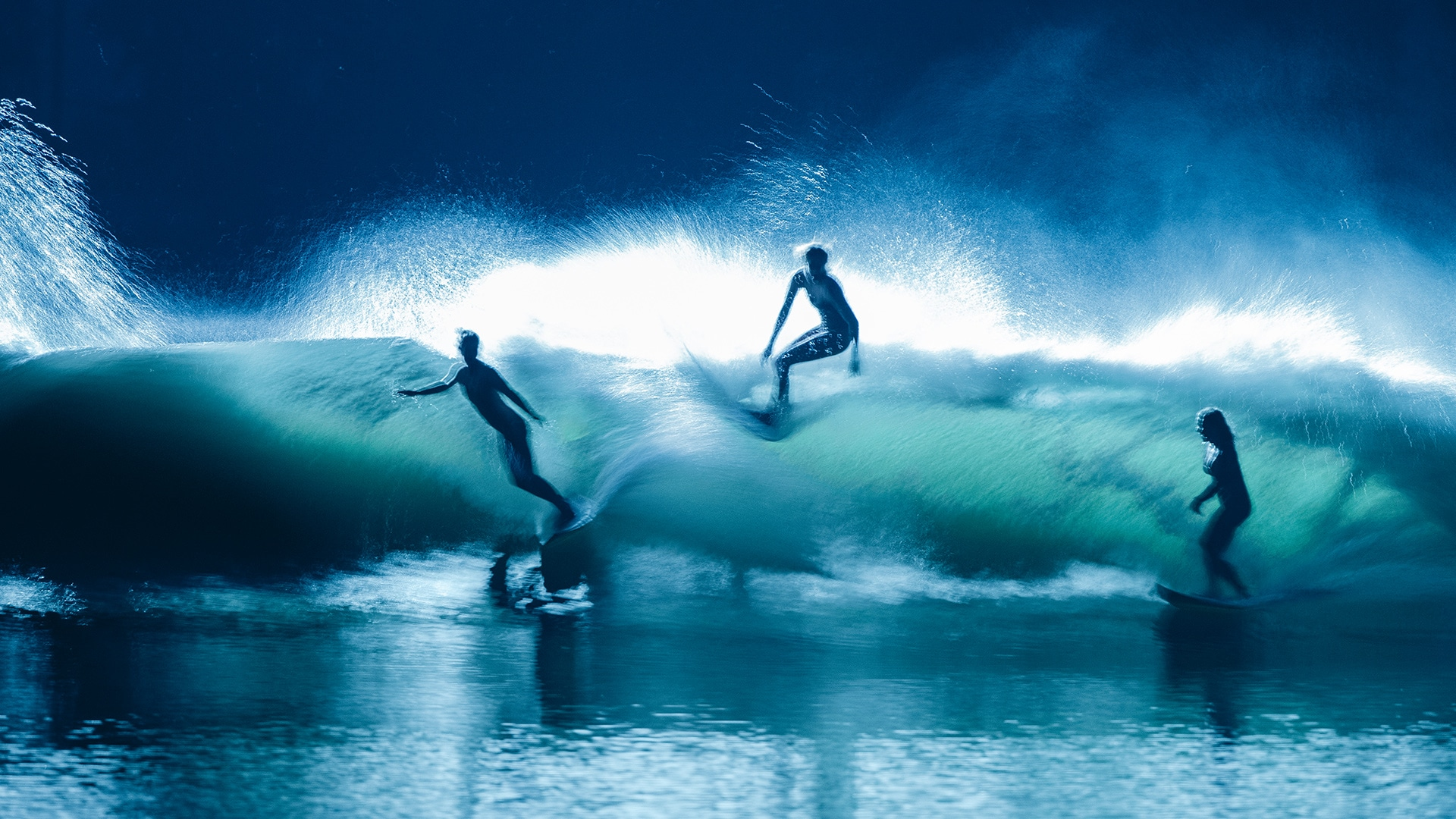 Three surfers in action.