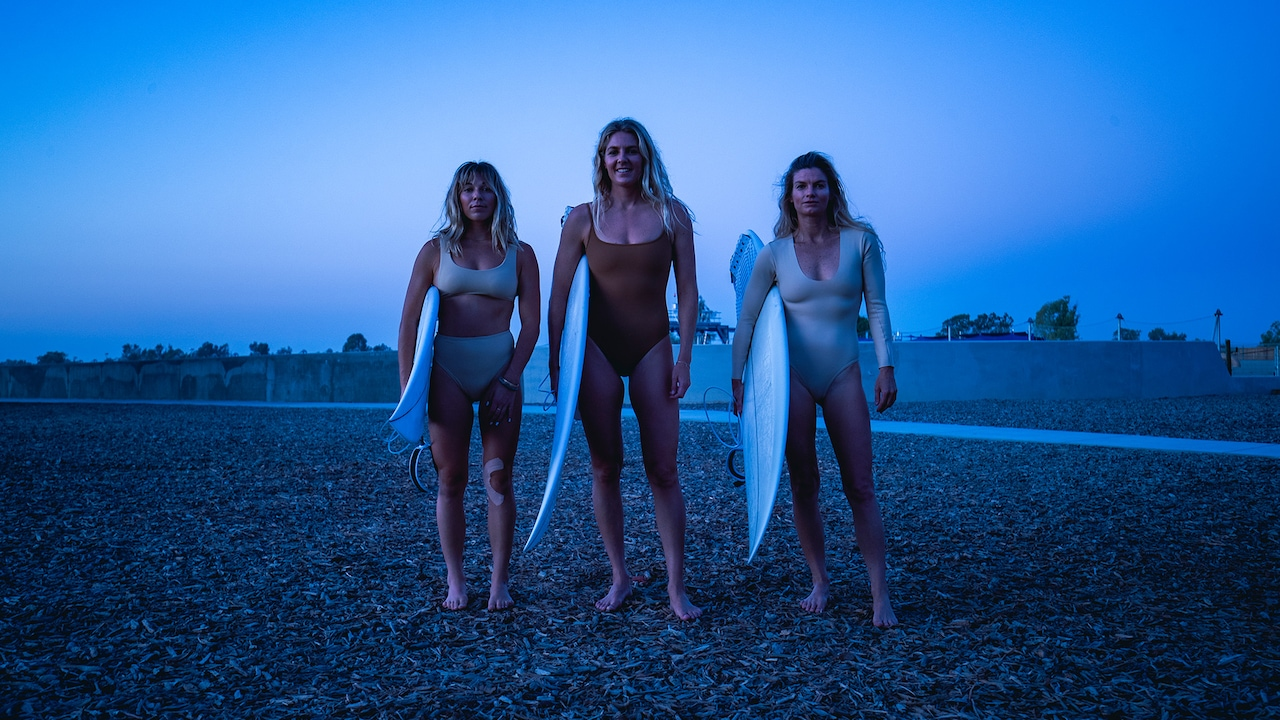 Stephanie Gilmore, Coco Ho and Leah Dawson with their surfboards.