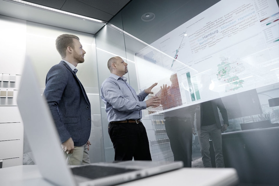 Employees looking at wall with integrated monitor