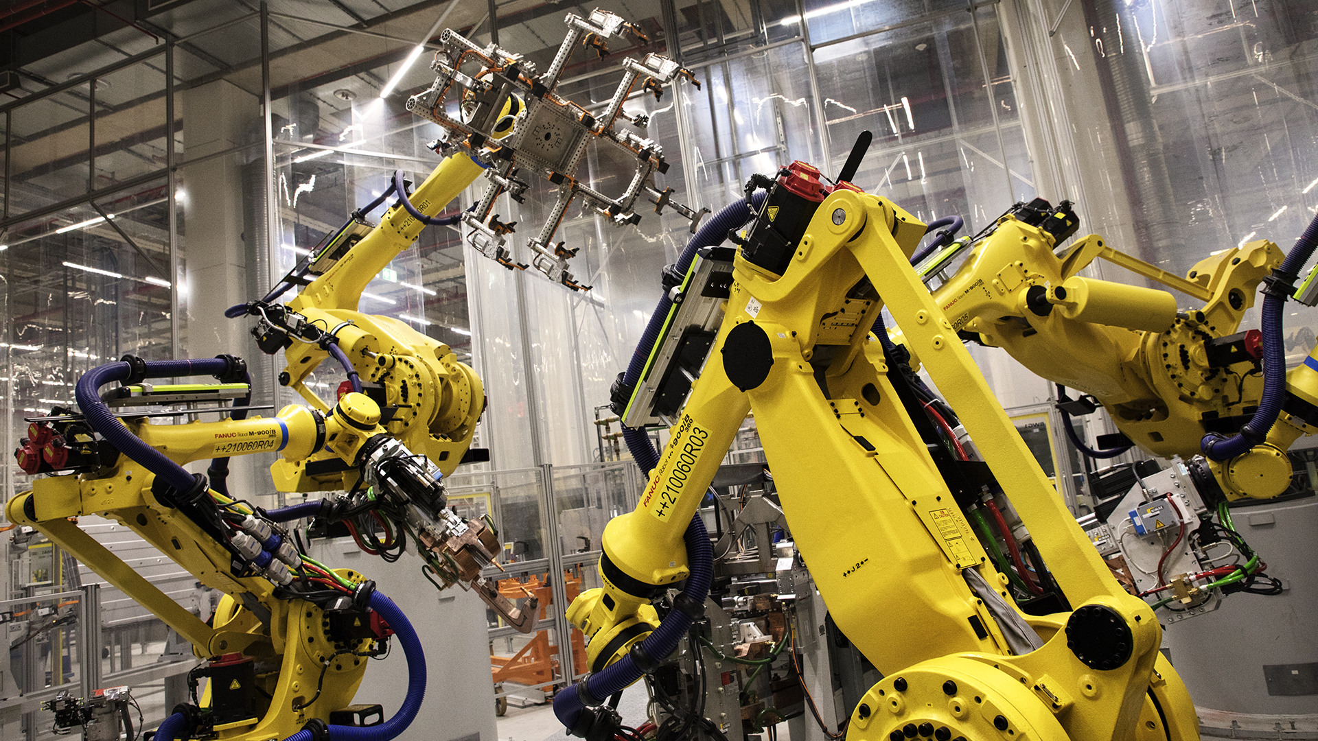 The robots in the body shop are so majestic and methodical in their movements that they evoke dinosaurs.